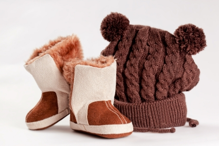 knitten: child winter boots and cap on a white background