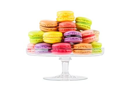 traditionele franse kleurrijke macarons in een glas taart staan op een witte achtergrond Stockfoto