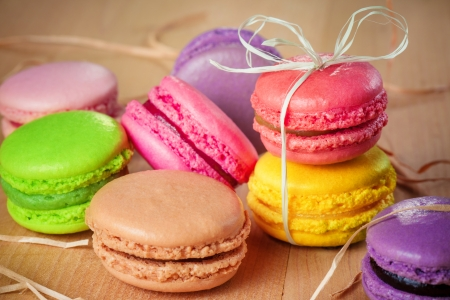traditional french colorful macarons with a bow on wooden table photo