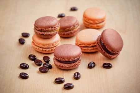 dark chocolate and caramel macaroons on wooden table photo