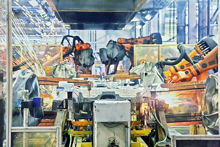production: robots welding in a car factory