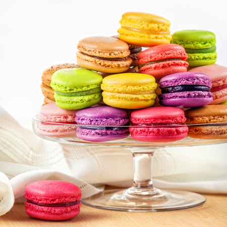 traditional french colorful macarons in a glass cake stand on wooden table Standard-Bild