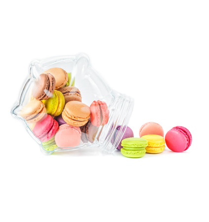 traditional french colorful macarons in a glass jar on white background photo