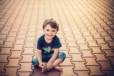 smiling little boy sitting on the ground photo