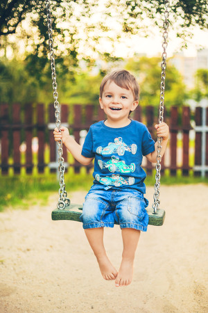 smiling boy on a swing photo