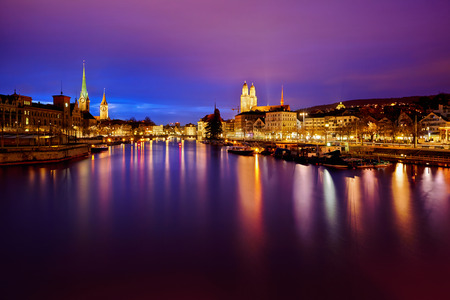 Zurich skyline en de rivier de Limmat 's nachts Stockfoto