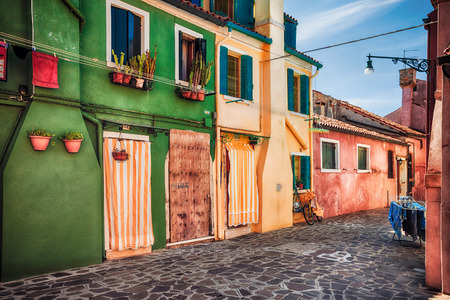old windows: Colourfully painted house facade with windows on Burano island, province of Venice, Italy