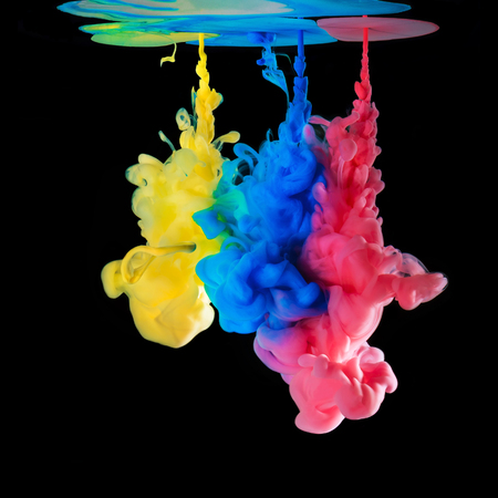 black ink: Colored ink drops in water on black background