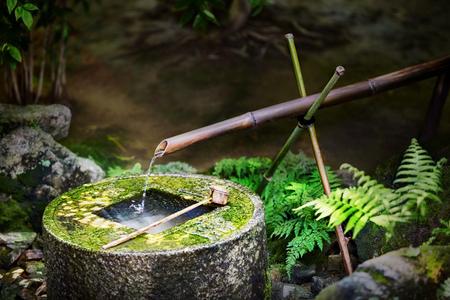 Tradicional fuente de bambú japonés Ryoan-ji en el templo TSUKUBAI Ryoan-ji en Kyoto, Japón. La cuenca prevista para el lavado ritual de las manos y la boca.
