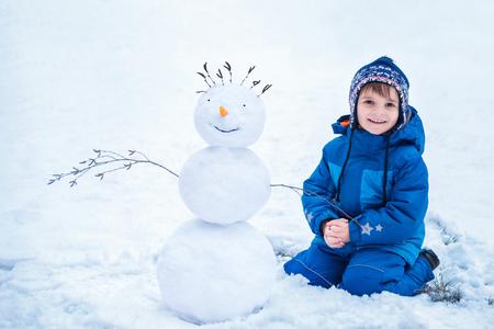 cute little boy sitting near the smiling snowman Banque d'images