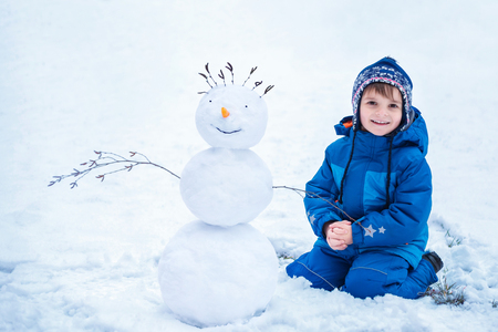 cute little boy sitting near the smiling snowman Standard-Bild