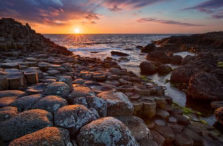 zachód słońca nad bazaltowymi kolumnami Grobla Olbrzymów znana jako miejsce światowego dziedzictwa UNESCO, hrabstwo Antrim, Irlandia Północna