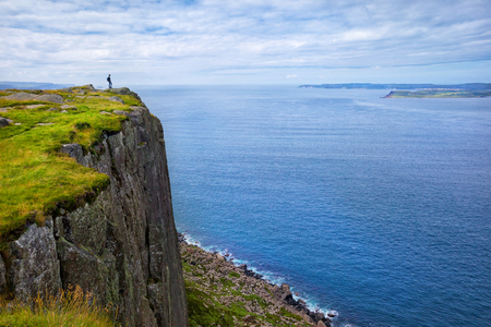 county fair: Lonely tourist with backpack standing on the cliff Fair Head and looking at Rathlin island, County Antrim, Northern Ireland, UK Stock Photo