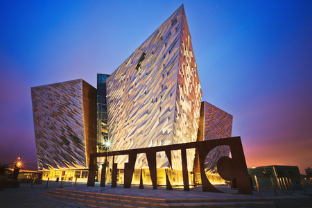 BELFAST, NORTHERN IRELAND - JUNE 28, 2017: Sunset over Titanic Belfast - museum, touristic attraction and monument to Belfasts maritime heritage on the site of the former Harland and Wolff shipyard. 에디토리얼