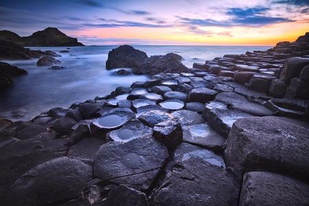 アントリム、北アイルランド、イギリス、素晴らしい Stookan 玄武岩の岩石形成ジャイアンツコーズウェイ、ポート ギャニー湾に沈む夕日