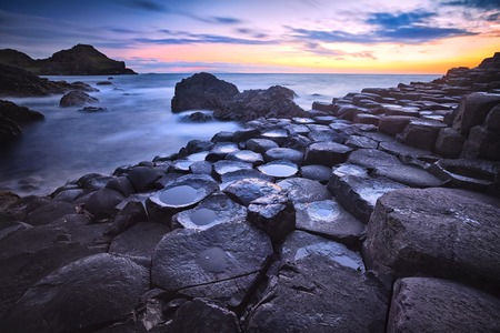 sunset over basalt rocks formation Giants Causeway, Port Ganny Bay and Great Stookan, County Antrim, Northern Ireland, UK