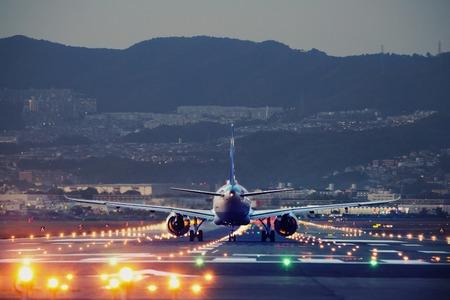 big plane landing at dusk at Osaka-Itami International Airport, Japan 免版税图像
