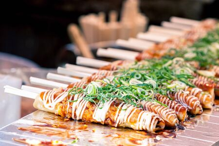 Okonomiyaki on wooden sticks with soy sauce and mayonaise topped with green onion at Nishiki market, Kyoto, Japan