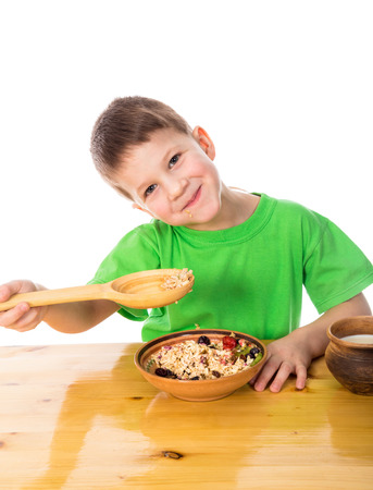 healty: Funny boy eating healty breakfast with oatmeal, isolated on white Stock Photo
