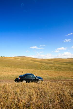 A car traveling in the steppe on the way photo