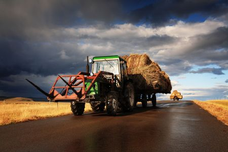 Tractor driving on the road loaded with straw