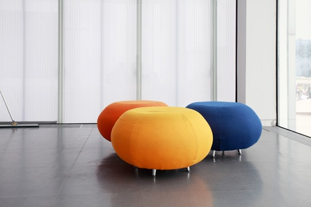 design studio: three different color rounded sofas isolated in morden house