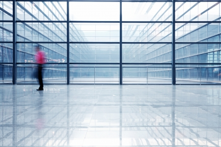building glass: people silhouette in hall of office building  Editorial