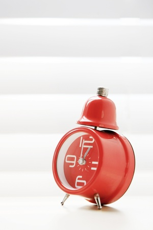 A red traditional alarm clocks thrown on white  photo