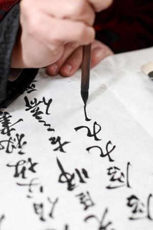 caligrafia: Hand holding Chines brush pen ��writing Chinese characters