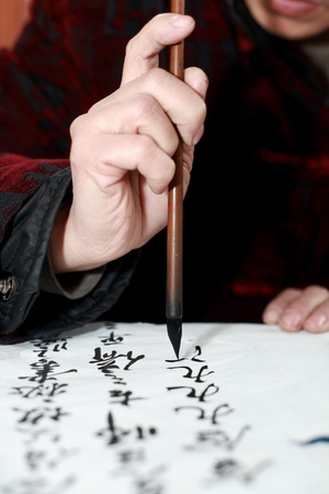 penmanship: Hand holding Chines brush pen ��writing Chinese characters