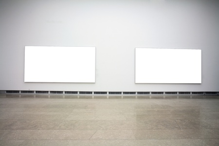 lit collection: empty frames in a room against a white wall   Stock Photo