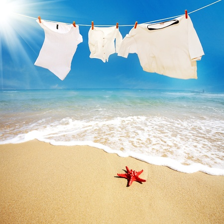 white T shirts hung on a line  on beach photo