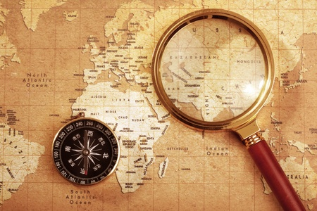 An old brass compass on a Treasure map background ,with Magnifier Stock Photo - 13537692