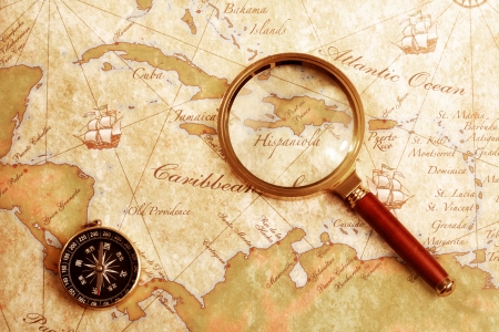brujula antigua: Un comp�s de lat�n antiguo en un fondo de mapa del tesoro, con lupa