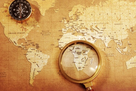 exploration: An old brass compass on a Treasure map background ,with Magnifier