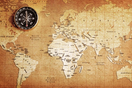 world travel: An old brass compass on a Treasure map background