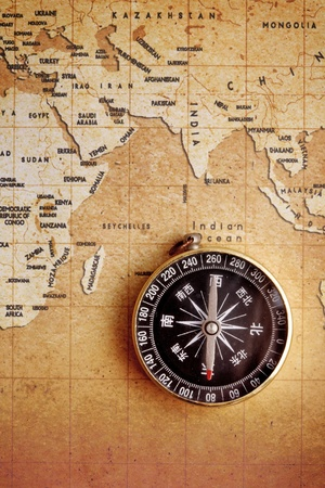 explore: An old brass compass on a Treasure map background