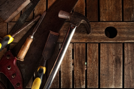 Dirty set of hand tools on a wooden panel photo