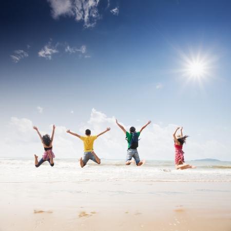 vrienden springen op het strand Stockfoto