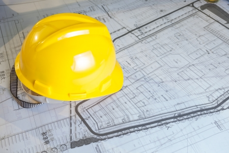 Construction plans with yellow helmet photo