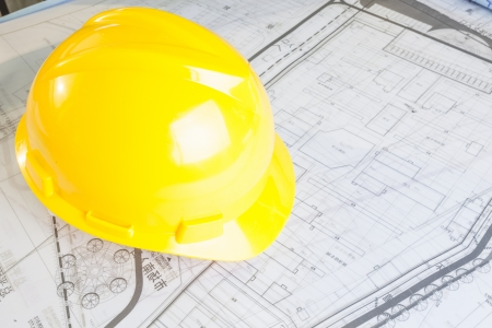 Construction plans with yellow helmet Stock Photo - 17293813