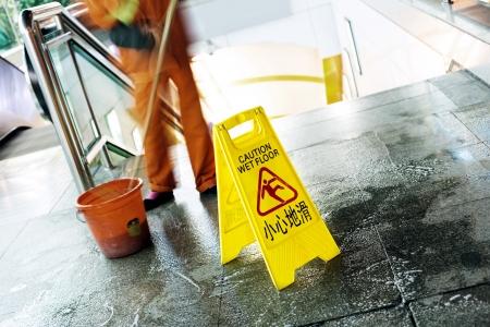 wet floor: cleaning in progress, and wet floor caution sign besides.