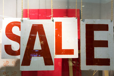 window display: clothes storefront window with sale poster