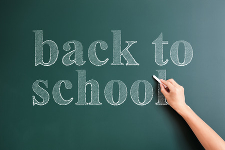title hands: writing back to school on blackboard
