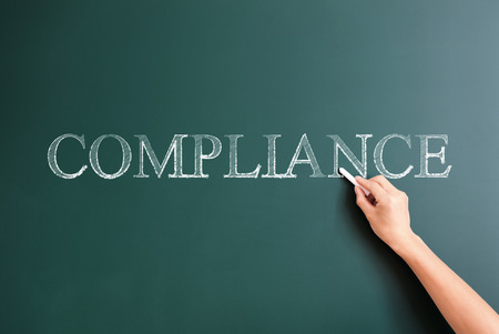 title hands: compliance written on blackboard