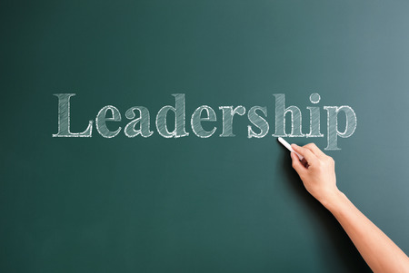 title hands: leadership written on blackboard
