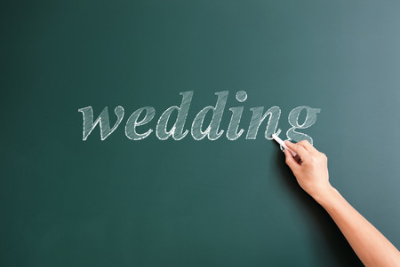 title hands: wedding written on blackboard Stock Photo
