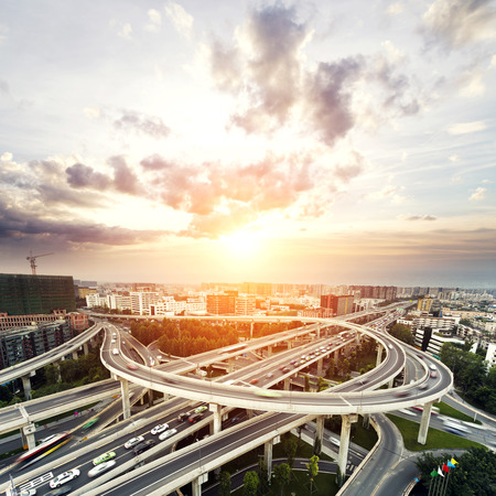 urban architecture: skyline and traffic trails on highway intersection
