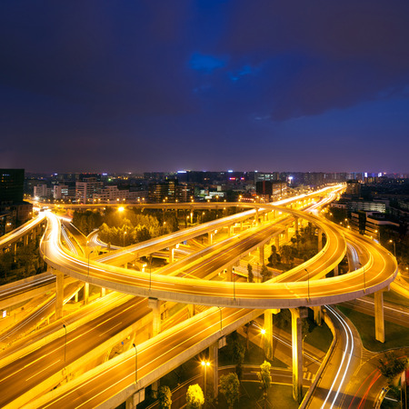 skyline and traffic trails on highway intersectionat night