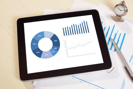 carta e penna: tavoletta digitale e smartphone con il rapporto grafico finanziario, carta, penna sul tavolo di lavoro. Sopra la vista colpo.